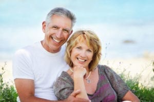 An older couple wearing affordable dental implants smiles with confidence.