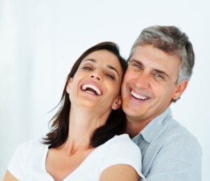 A couple smiling and showing white teeth after visiting a metal-free dentist.